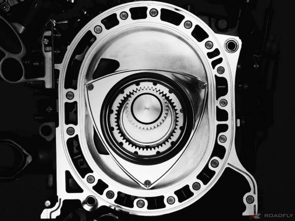 Роль поршней в двигателе Ванкеля выполняет треугольный ротор, вращающийся на валу внутри цилиндра